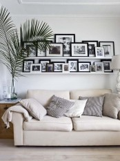 a neutral living room personalized with long white ledges that show off black and white photos of the whole family