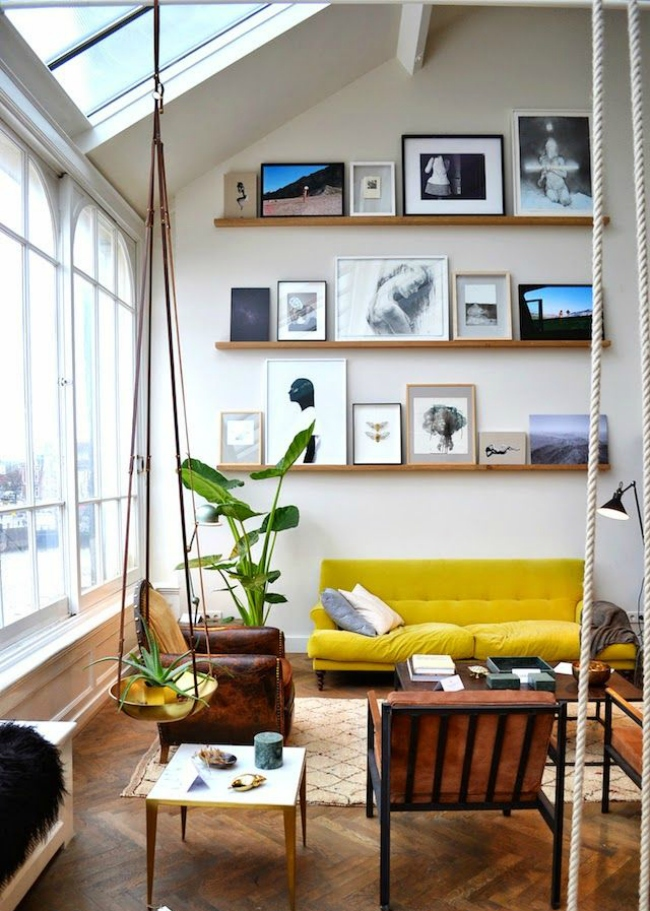 a bold double height living room with lots of natural light, bold furniture, ledges with cool and bold artworks plus potted plants and greenery