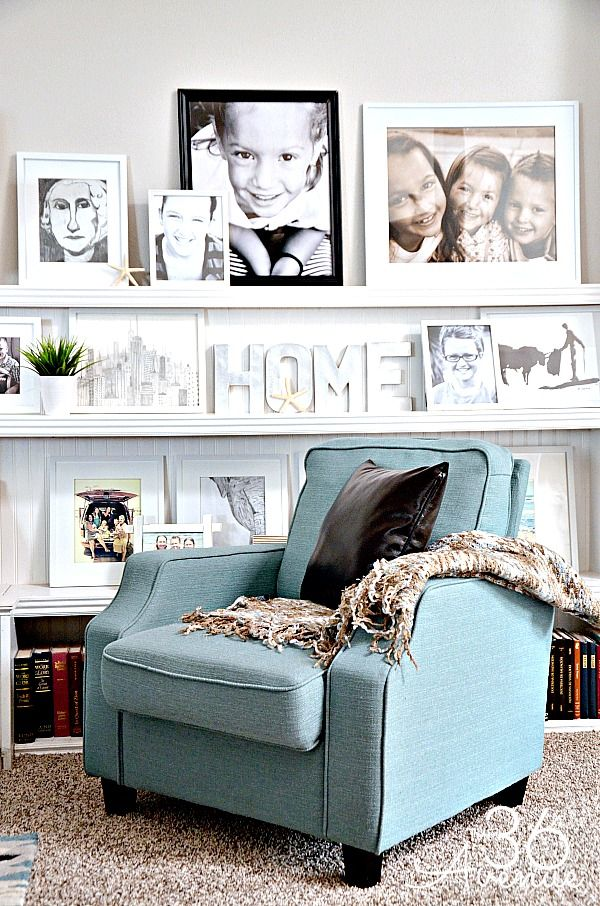 a chic reading nook with bookshelves and long white ledges with artworks, photos, potted greenery and monograms