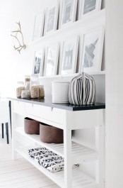 a Nordic space with white ledges and black and white photos in matching frames is a cool and stylish idea