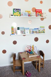 a playroom with ledges over the table with kids' books – this is a simple and cool idea to store books without using floor or table space