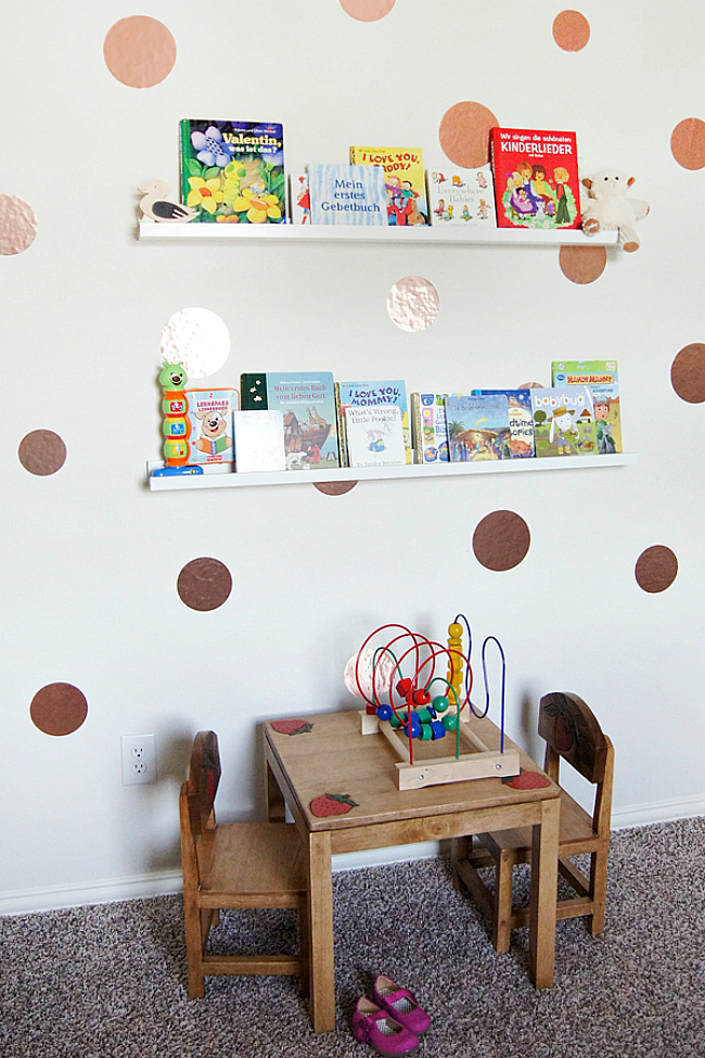 a playroom with ledges over the table with kids' books   this is a simple and cool idea to store books without using floor or table space