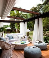 a modern outdoor terrace with lots of curtains for privacy and to block sunlight, modern outdoor furniture, a wicker chair and blue ottomans