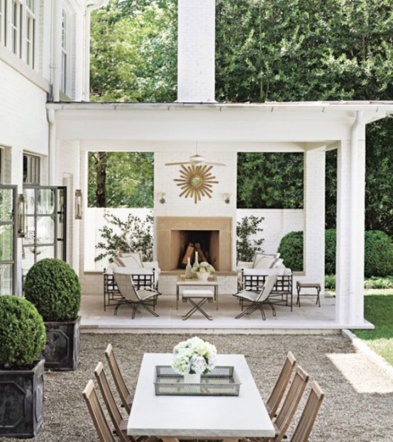 a modern elegant space with a fireplace and living room furniture with white upholstery, a dining space with wooden chairs and a large table