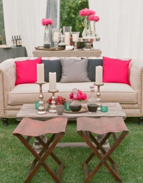 a modern neutral terrace with a sofa, a coffee table, leather stools and a console table spruced up with bright pink touches