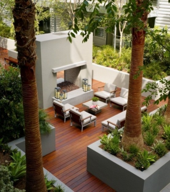 a modern tropical terrace with a two side fireplace, stylish modern furniture, potted plants and even palm trees around