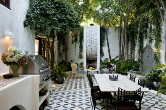 a modern terrace with a mosaic black and white floor, a fireplace, a dining set with black chairs and a mini outdoor kitchen