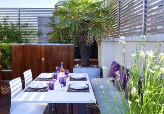 a modern dining space done in white and purple, with potted greenery and some blooms is very welcoming