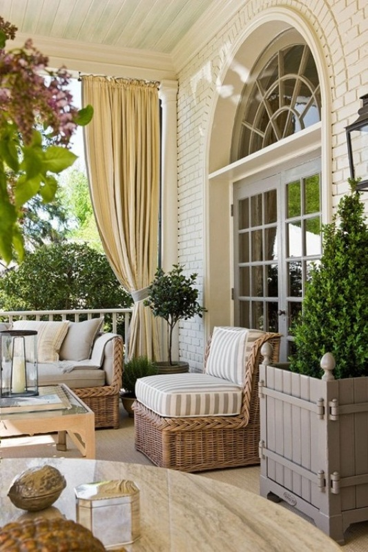 a modern neutral terrace with a Mediterranean feel, with potted greenery and plants, with wicker and wooden furniture
