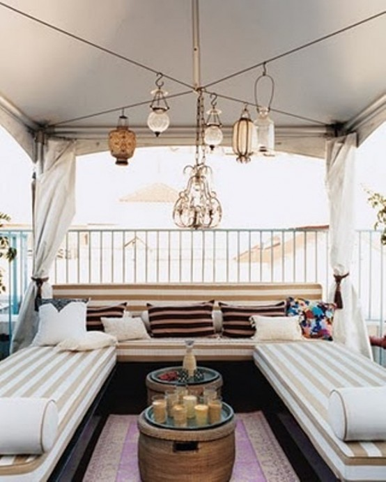 a modern take on a boho Moroccan terrace with striped sofas, pillows and a large Moroccan chandelier with lanterns