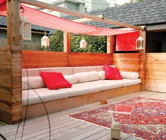 a bright modern terrace with a large wooden bench with a red canopy and red pillows plus a boho rug is a bold and cool place to be