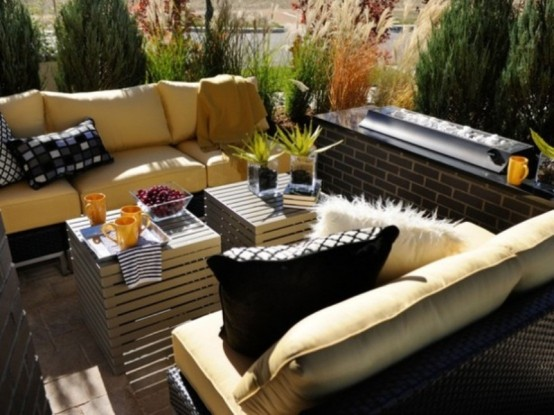 a small modenr rooftop terrace with comfy yellow sofas, crate tables and a drink cooler by the side is a dream