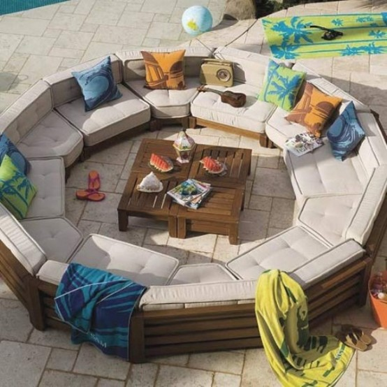 a modern round conversation put with colorful pillows and blankets plus small crate coffee tables in the center