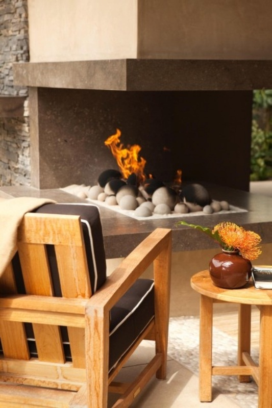 a modern terrace with an open fireplace with pebbles and simple wooden upholstered furniture is a lovely place to stay