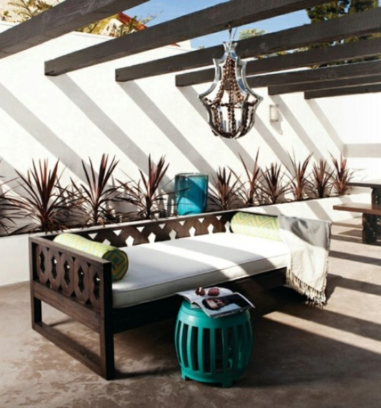 a bold modern space with dark stained wooden beams, a catchy chandelier, a carved wooden bench and a turquoise table