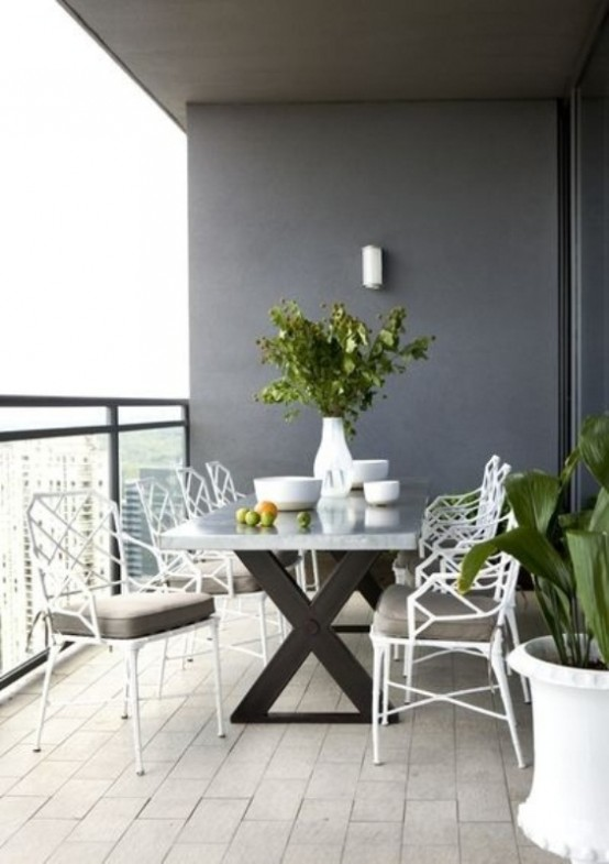 a modern balcony dining space with a trestle table and white metal chairs plus potted greenery for a fresh feel