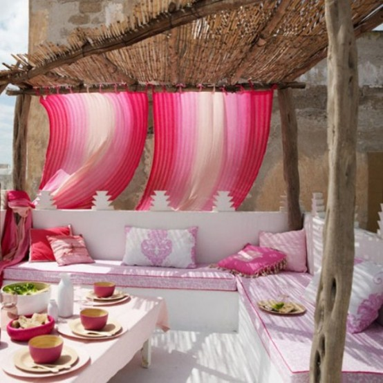 a modern super bright terrace with a tropical feel, a wicker roof, bright pink curtains and pillows and pink tableware and greenery