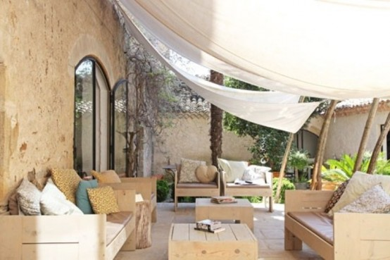 a modern terrace with light-colored wooden furniture, printed pillows and potted greenery plus curtains