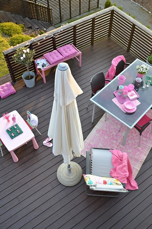a modern blacony terrace with simple furniture, a kids' drawing nook, bright pink touches and a potted plant for a fresh feel