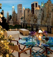 a modern rooftop terrace with a wooden bench, a glass table with colorful glasses and modern chairs and stunning views
