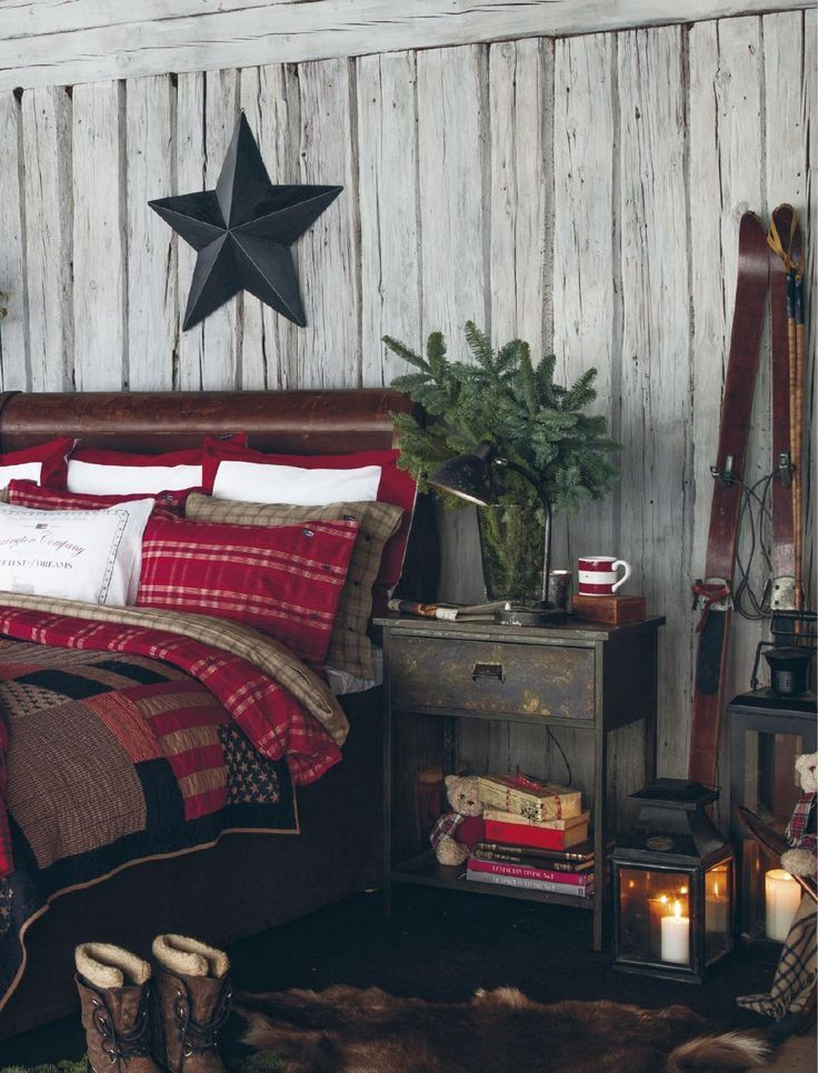 plaid bedding, a faux fur rug, an evergreen arrangement and lots of candle lanterns for a cozy winter feel in the bedroom