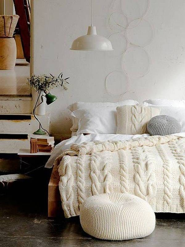 white knit bedding and pillows and an ottoman make the bedroom more winter like and very chic