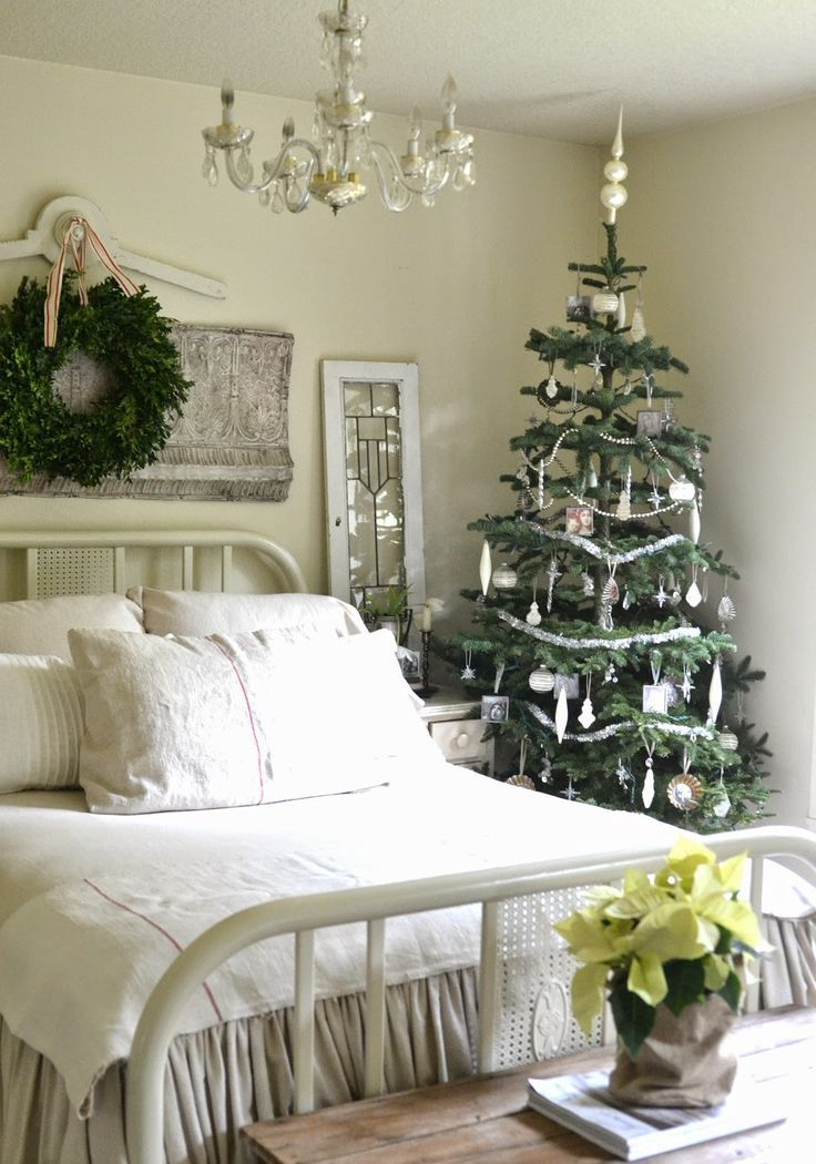 a neutral bedroom dressed up for a Christmas tree with ornaments and a greenery wreath and with potted blooms