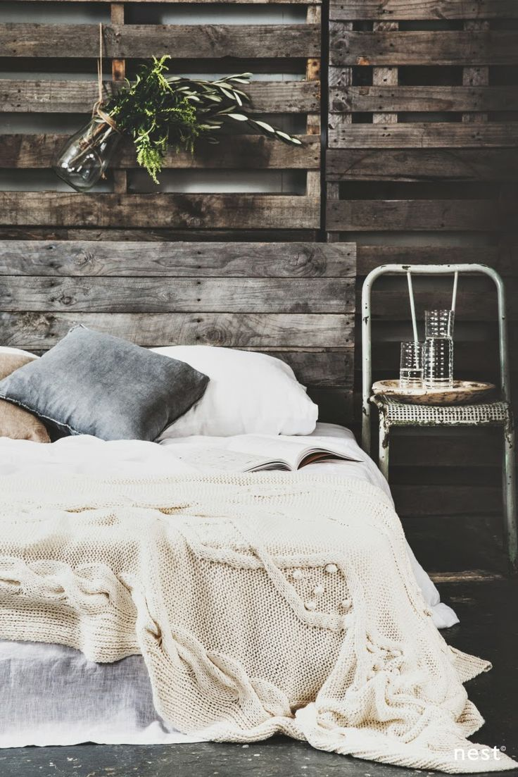 a white chunky knit blanket and some greenery in a jar for a stylish winter bedroom look