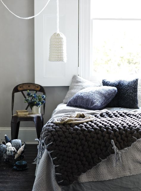 knit pillows in various shades, various knit and chunky knit blankets and a knit pendant lamp