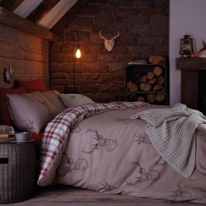 mauve and plaid bedding with deer prints, a knit blanket and some firewood in crates make the bedroom winter ready and cozy