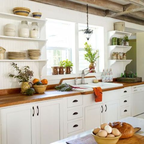 Exposed beams on a farmhouse kitchen works quite good with white cabinetry  and shelves.