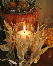a pillar candle in a candleholder wrapped with corn husks and corn cobs is very rustic and very cozy