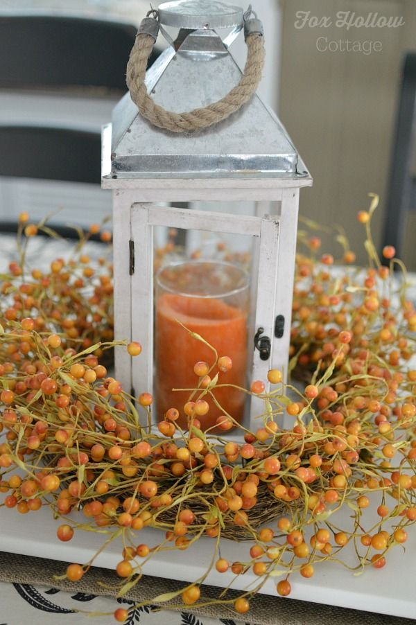 a faux berry wreath surrounding a candle lantern with an orange candle is a lovely and easy rustic centerpiece for the fall