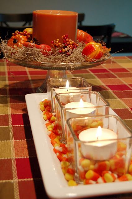 a plate with candy corn and candles in glasses is a bright fall centerpiece you can easily make last minute
