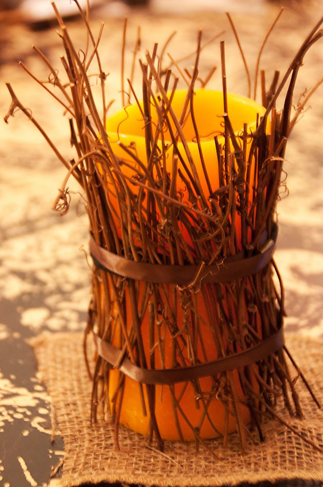 a candle with twigs and ribbon is a cool rustic fall decoration to use and you can DIY it last minute