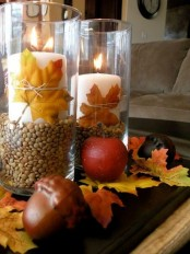 a fall centerpiece of acorns, fall leaves and pillar candles in glasses with corn and fall leaves is lovely and easy to DIY