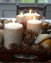 a rustic fall centerpiece of a tray with pinecones, candles wrapped with burlap and acorns is a lovely idea for the fall
