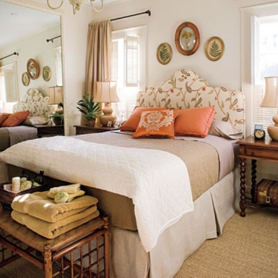 a bright fall-inspired bedroom with a floral upolstered bed, touches of neutrals and muted shades plus orange accents