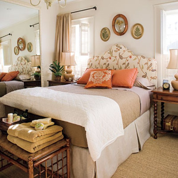 a bright fall inspired bedroom with a floral upolstered bed, touches of neutrals and muted shades plus orange accents