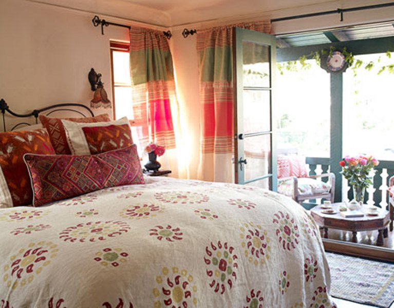 a bright fall bedroom with touches of green, red, burgundy and neutrals and much pattern for a countryside feel