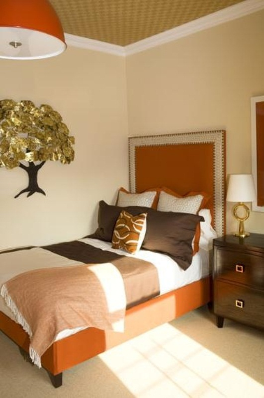 a fall colored bedroom with an orange bed, chocolate browns and muted greens plus neutrals