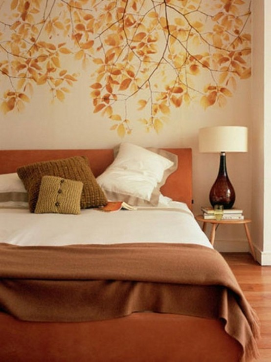 a fall-colored bedroom with a leafy wall, an orange bed, muted color pillows, a table lamp with a brown glass base