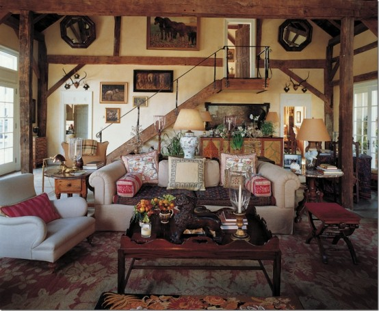 a barn living room with wooden beams and pillars, with a vintage gallery wall, neutral seating furniture, stained stools and tables and chic lamps