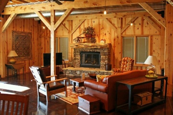a wood clad barn living room with a fireplace clad with stone, leather and wood furniture, lamps and hanging bulbs is cozy