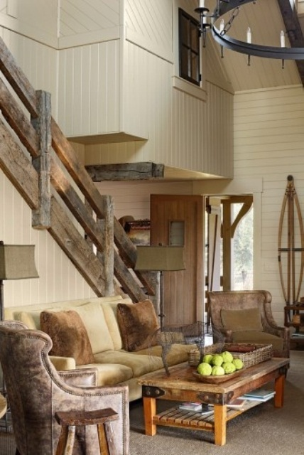 a barn living room with white planked walls, neutral seating furniture, a low coffee table, a large chandelier and reclaimed wood railing is chic and welcoming