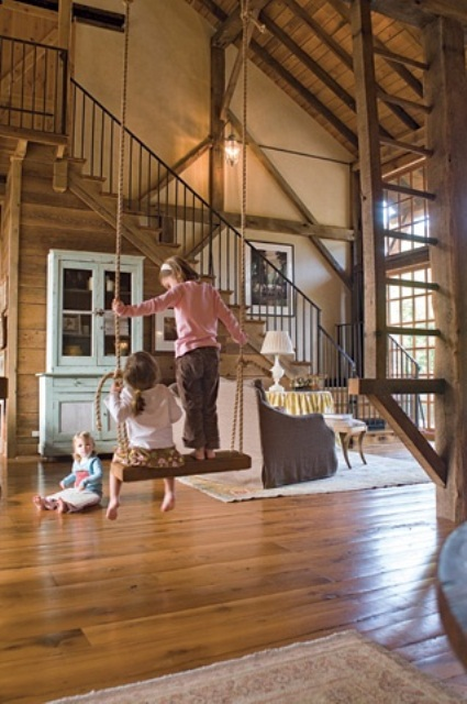 a vintage barn living room clad with wood, with wooden stairs, a swing, neutral and pastel vintage furniture and lots of natural light