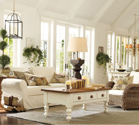a white barn living room with white seating furniture, lots of potted greenery, a jute rug, lamps and candles is a very lovely idea