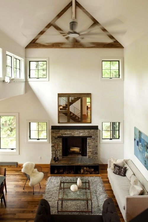 a stylish neutral barn living room with a double-height ceiling, a fireplace clad with stone, neutral seating furniture, a glass table and faux fur is cool