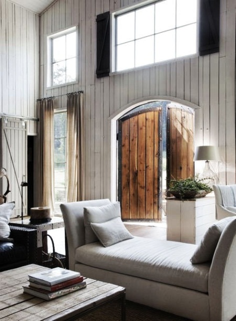 a relaxed barn living room with white planked walls, elegant white seating furniture, a low planked wooden table and neutral textiles is amazing