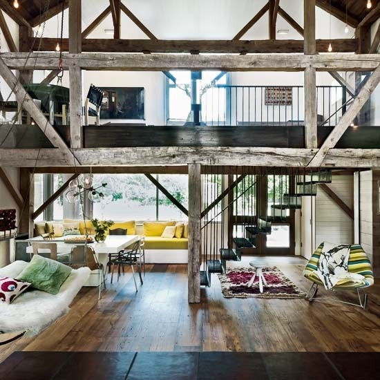 a barn living room with lots of pillars and beams of reclaimed wood, with neutral and colorful furniture, colorful and printed textiles is a cool idea
